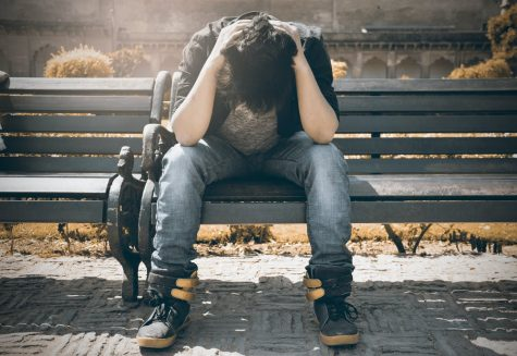 A boy stressing on a bench